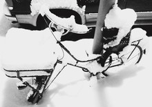 Snow Covered Bicycle On Street During Winter