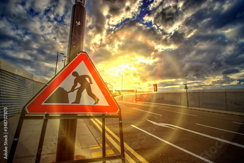 Road Sign Against Cloudy Sky During Sunset