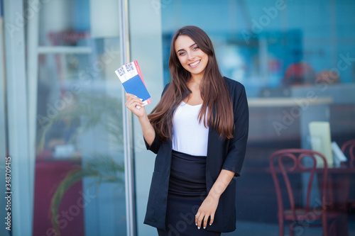 Fotomural Woman near the airport holding a passport and plane tickets