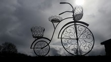 Silhouette Penny Farthing Bicycle Against Cloudy Sky At Dusk
