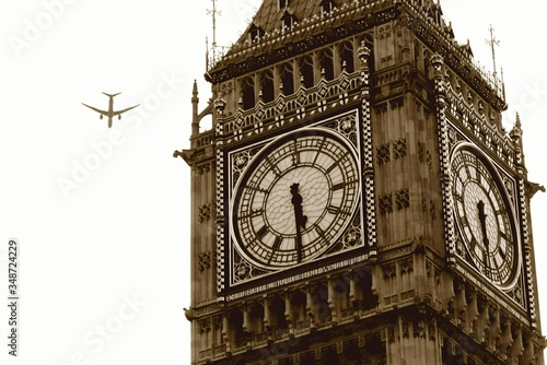 Low Angle View Of Airplane Flying By Big Ben Against Sky Canvas Print