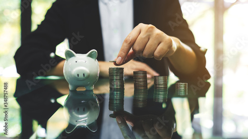 Obraz na plátně Businesswoman stacking coins with a white piggy bank on the table for saving mon