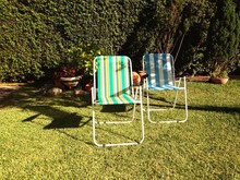 Deck Chairs On Grassy Field