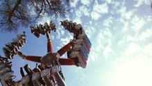 Low Angle View Of Amusement Park Ride Against Cloudy Sky