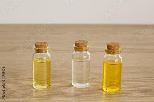 Fotografie, Obraz Transparent bottles of almond oil, jojoba oil and rose water for the production