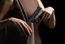 Woman Hand Pulling A Pistol Out Of Handbag On Black Background.