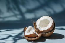 Half A Coconut And Pieces Of Coconut On A Blue Background.