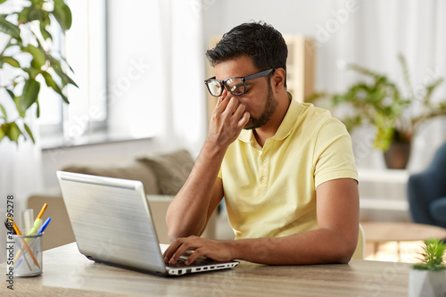 remote job, technology and people concept - tired young indian man in glasses wi Fototapeta