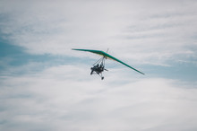 The Motorized Hang Glider In The Blue Sky.