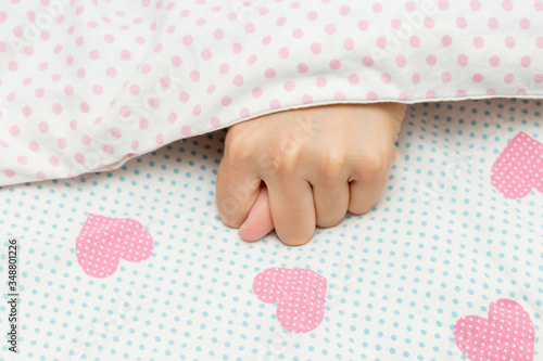 Beautiful female hand shows a fig sign under a white blanket, hands showing thumb Wallpaper Mural