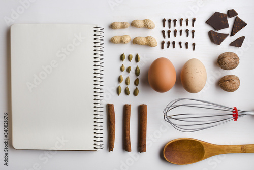 Top view of blank notebook, kitchen utensils, eggs, cinnamon, cardamon, chocolate, peanuts, cloves, nuts on the white kitchen table Canvas Print