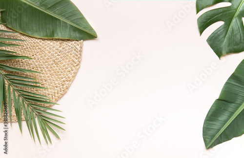 Obraz Round wicker stand and palm leaves on pink background. Fltlay style concept with text place. - fototapety do salonu