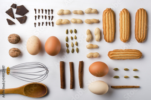 Top view of biscuits, cinnamon, cardamon, peanuts, eggs, nuts, chocolate, kithcen utensils in a row, abreast Canvas Print