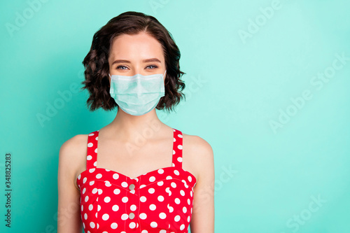 Close up portrait of fascinating young wonderful lady posing in front of camera show covid-19 self-isolation wear fabric mask isolated with teal background