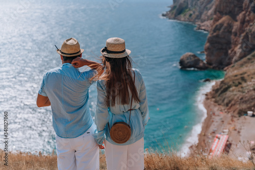 Carta da parati The couple stands with their back to the audience and look down at the beautiful seascape