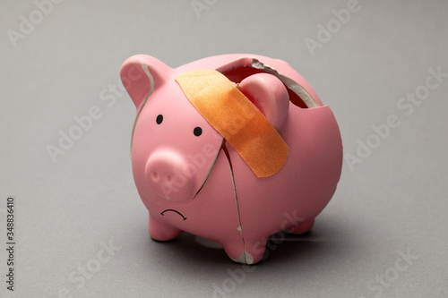 Broken piggy bank with band-aid on gray background Fotobehang