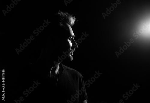 Dramatic profile portrait of male person on dark background - fototapety na wymiar