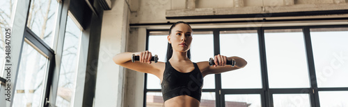Obraz Panoramic shot of sportswoman training with dumbbells in gym - fototapety do salonu