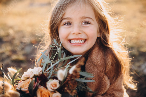 Fototapeta Portrait of a small stylish beautiful model girl who stands in the autumn mountains at sunset and holds a bouquet of flowers in her hands obraz