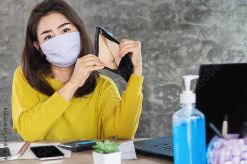 Obraz poor Asian woman wearing protective mask hand open empty purse having financial problem during self-quarantine from covid-19 virus pandemic - fototapety do salonu