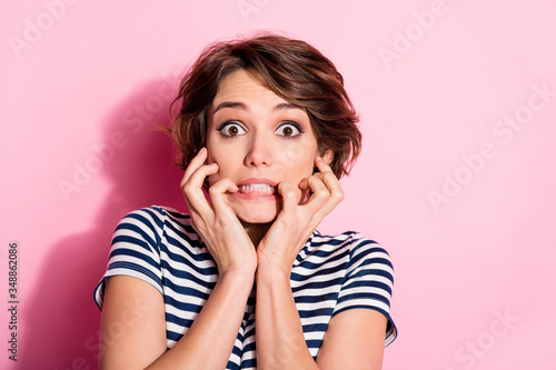 Fototapeta Closeup photo of attractive scared lady short hairdo eyes full of fear biting fingers failure watch horror movie wear casual white blue t-shirt isolated pastel pink color background obraz