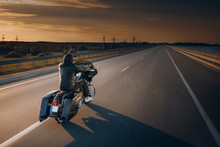 Motorcycle Driver Riding Alone On Asphalt Motorway. Biker In The Motion At The Empty Road