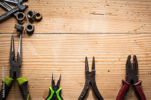 VARIOUS PLIERS AND SCREW WRENCHES LAYING ON A WOODEN TABLE Fototapet