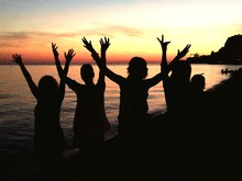 Silhouette Friends With Arms Raised Standing At Beach At Sunset