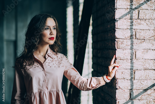 Valokuvatapetti Beautiful young woman with curly dark hair and red lips in a powdery dress is standing near the window in the loft studio