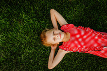 Young Blond Cute Girl In Red Squared Summer Swimsuit Laying On Green Grass