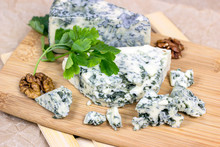 Slices And Triangles Of Danish Blue (dorblue) Cheese With Mold On A Light Wooden Board  Background.