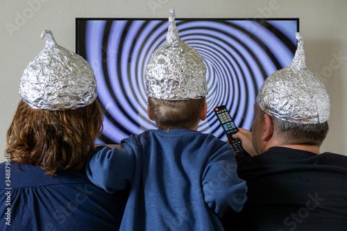 Family looks at the TV and has aluminium hats #348879818