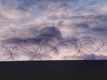 Low Angle View Of Barbed Wire Fence On Wall Against Sky