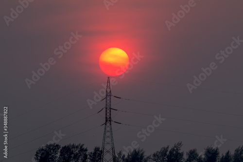 Fotografie, Obraz Low Angle View Of Silhouette Electricity Pylon Against Sun During Sunset