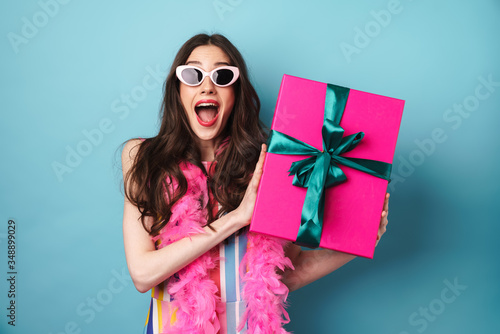 Foto Image of surprised woman in sunglasses holding gift box