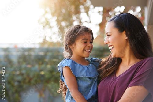 Smiling Hispanic Mother Holding Daughter Laughing In Garden At Home Billede på lærred