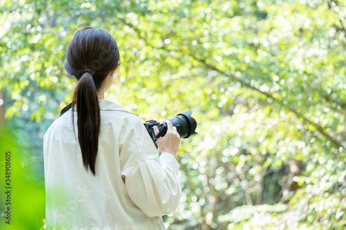 Fototapeta 自然の中でカメラを構える若い女性 obraz