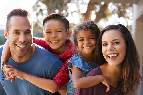 Portrait Of Smiling Hispanic Family With Parents Giving Children Piggyback Rides Canvas Print