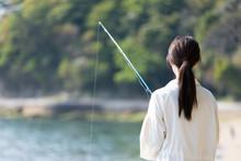 海辺で釣りを楽しむ若...