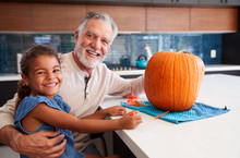 Portrait Of Grandfather And Granddaughter Carving Halloween Lantern From Pumpkin At Home