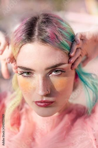 Fotografía Retrato de una mujer joven caucásica, de piel blanca con algunas pecas en la nariz, con el cabello turquesa y rosa