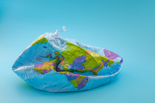 Global Warming, Climate Catastrophe And Environmental Trouble Concept With Deflated Globe Isolated On Blue Background