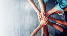 Close Up Top View Of Young Business People Putting Their Hands Together. Stack Of Hands. Unity And Teamwork Concept. Left Copy-space.