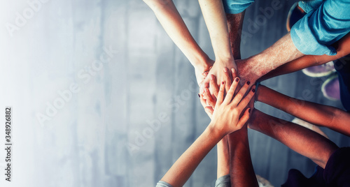 Fotomural Close up top view of young business people putting their hands together