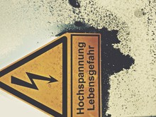 Close-up Of High Voltage Sign On Glass