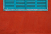 Closed Blue Shutters On A Red Wall.