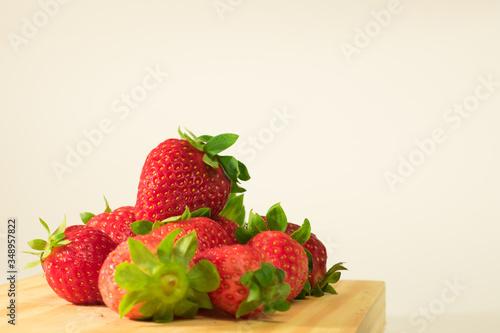 Photo Fresas en tabla de madera con fondo blanco.