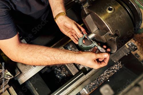 Obraz na plátně Professional machinist : man operating lathe grinding machine