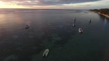 Aerial View Of Boats Anchored In Mauritius Island Lagoon With Foamy Waves Of Indian Ocean Rolling In , Flying Alongside Coastline, Evening Time