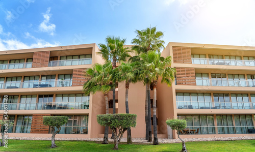 Fotografía A modern hotel with palm trees, green grass and blue skies, sun